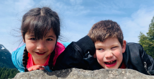 two children laying on a rock