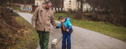 Father and son walk dog
