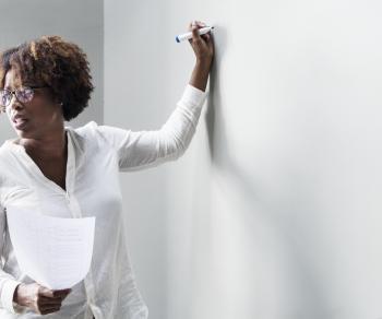 African women standing next to black board