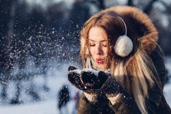 Woman blowing snow out of her hands