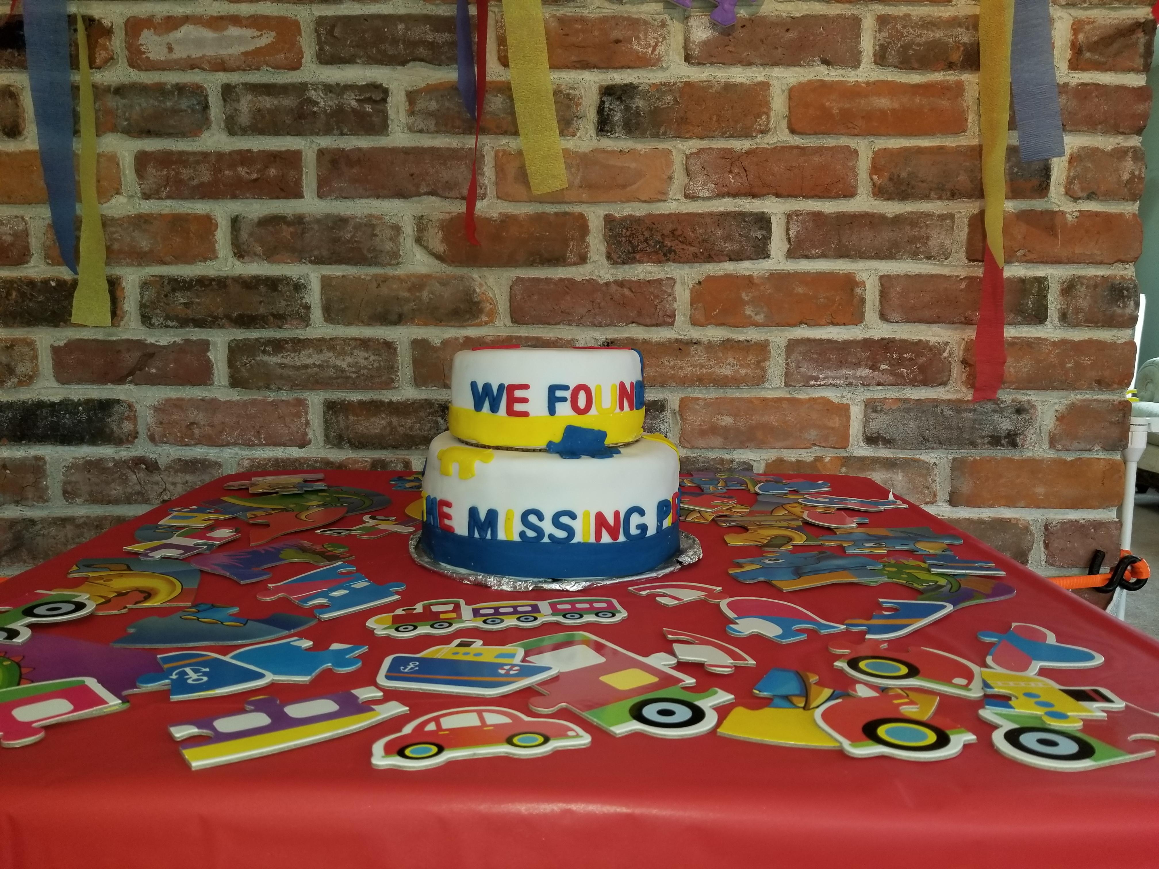 """Cake decorated with puzzle pieces, says """"We found our missing piece,"""" sits on table with other puzzle decorations"""