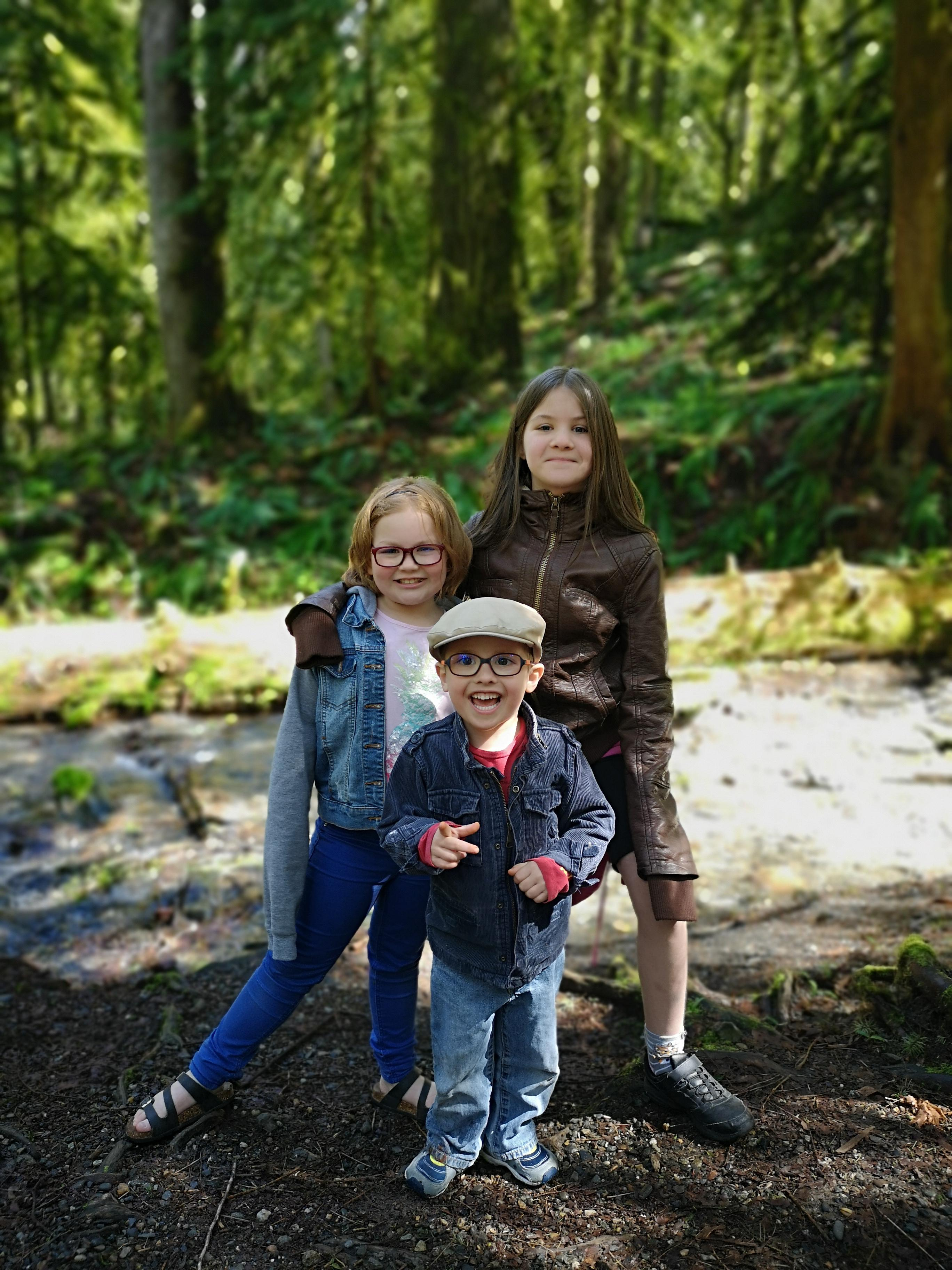 Three siblings smile at the camera. They are standing in a sunny forest.