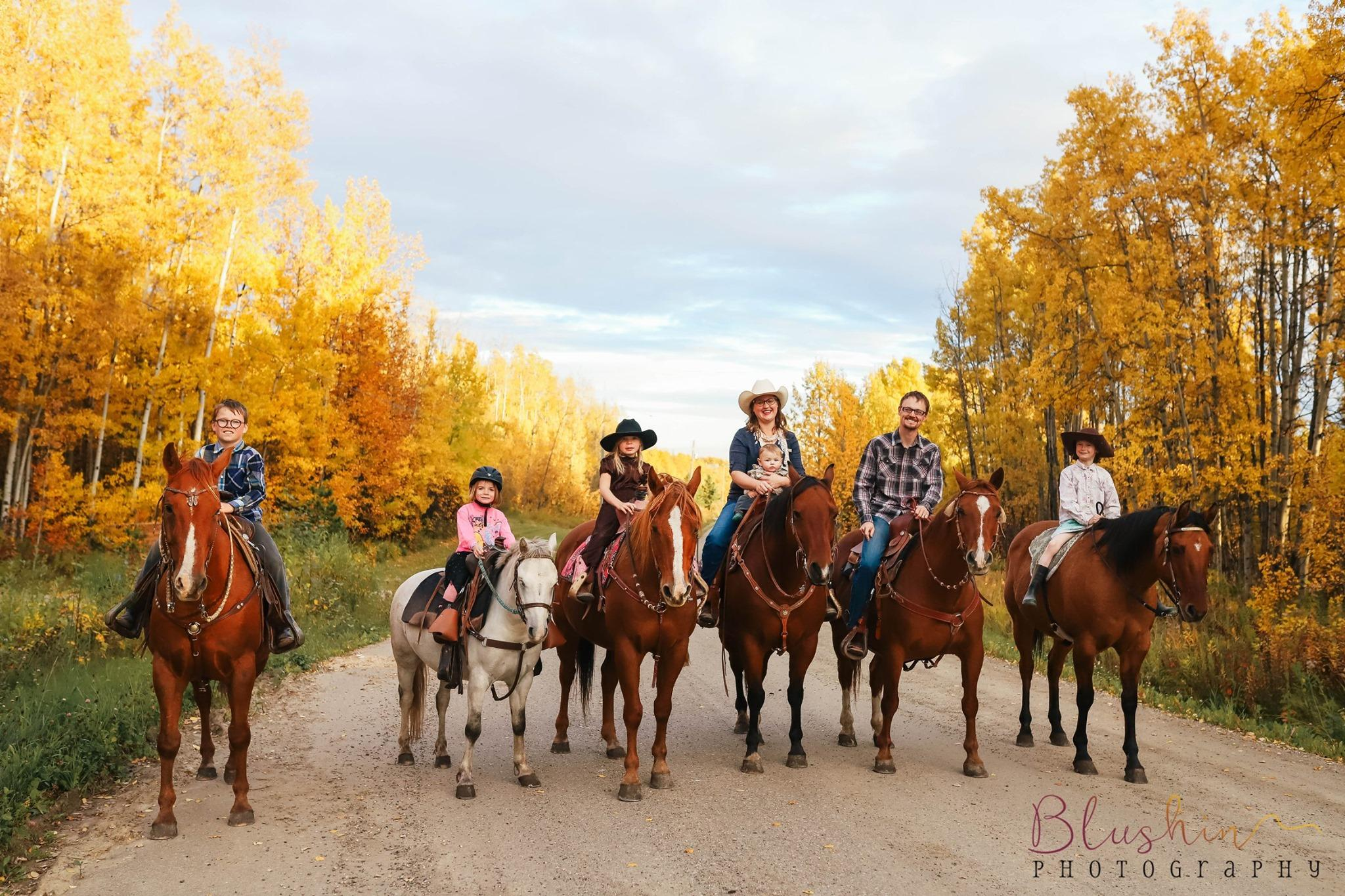 giesbrecht family, all on horses, stands in a row