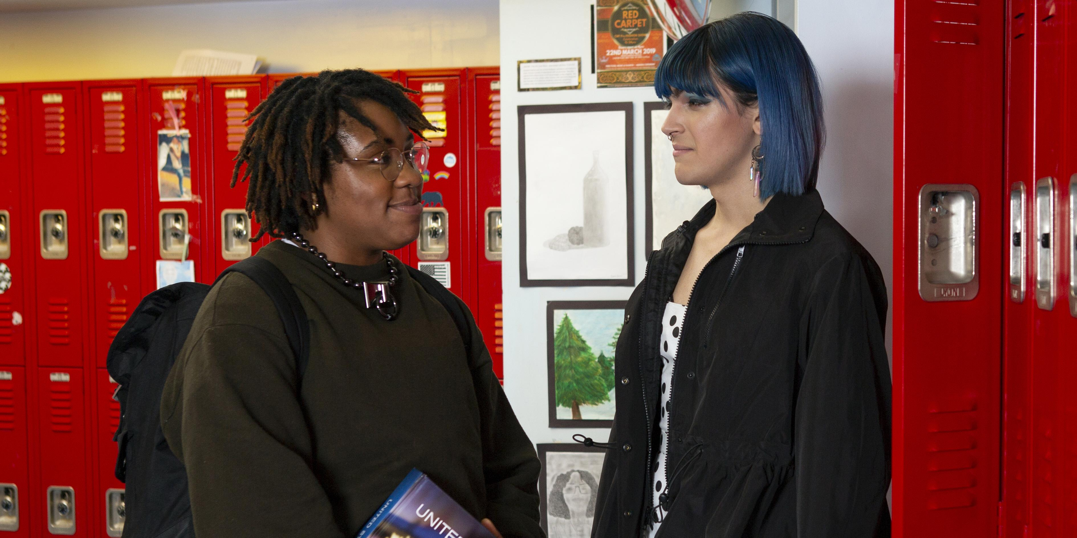 Two students talking in a hallway